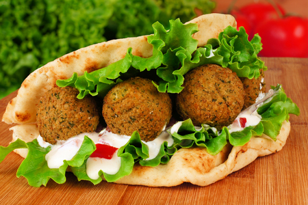 sandwich: Falafel with vegetables and  tzatziki sauce in pita bread close-up on wooden table