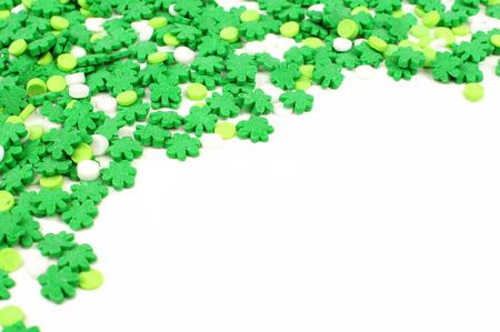 St Patricks Day corner border of green shamrock candy sprinkles over white photo