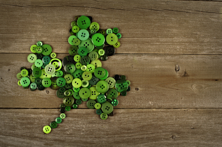 St Patricks Day shamrock made of buttons against an old wood background
