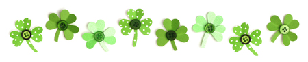 saint paddy's: St Patricks Day border of varied handmade paper and button shamrocks over a white background Stock Photo
