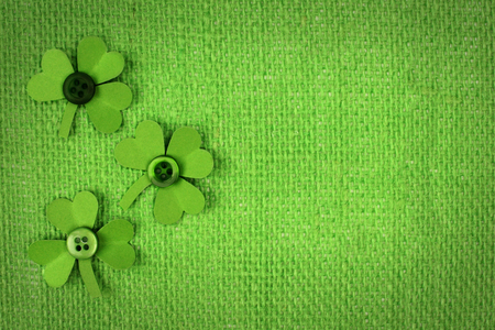 St Patricks Day green burlap background with paper shamrock border