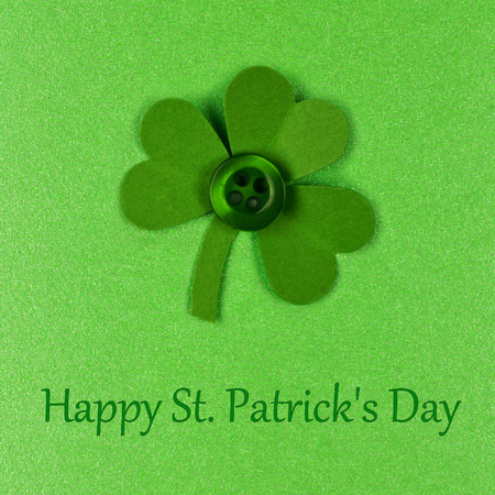 cloverleaf: Happy St Patrick Day text with handmade shamrock on a green paper background