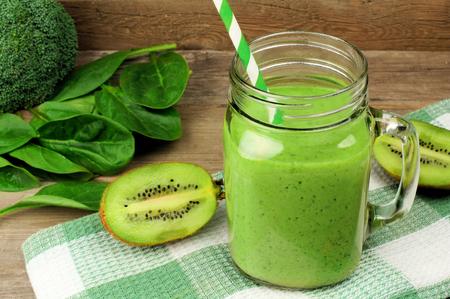 ほうれん草と木材に対する格子縞布で瓶マグカップのキウイと健全な緑のスムージー