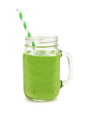 green background: Healthy green smoothie with straw in a jar mug isolated on white