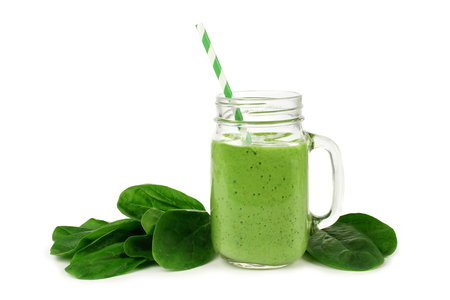 Healthy green smoothie with spinach in a jar mug isolated on white