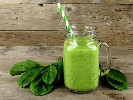 juice fresh vegetables: Healthy green smoothie with spinach in a jar mug against a wood background Stock Photo