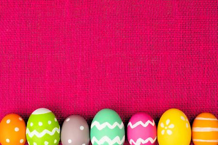Colorful Easter egg bottom border over a pink burlap background Stok Fotoğraf - 36503967