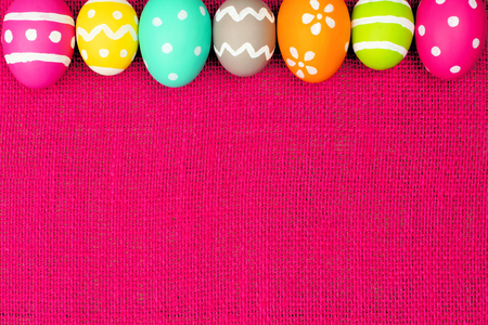 Colorful Easter egg top border over a pink burlap background