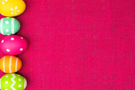 Colorful Easter egg side border over a pink burlap background