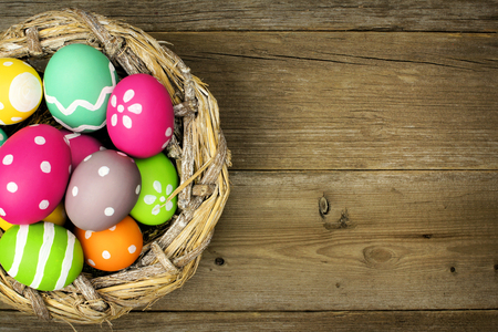 painted wood: Easter eggs in a nest over an old wood background Stock Photo
