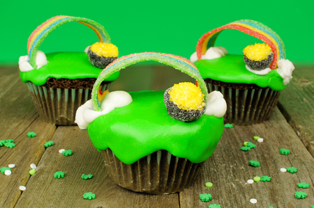 saint paddy's: St Patricks Day cupcakes with pot of gold and rainbows on wood with green background Stock Photo