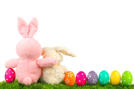 pascuas navide�as: Abrazando conejitos de Pascua en el c�sped con colores frontera huevo sobre blanco detr�s vista Foto de archivo