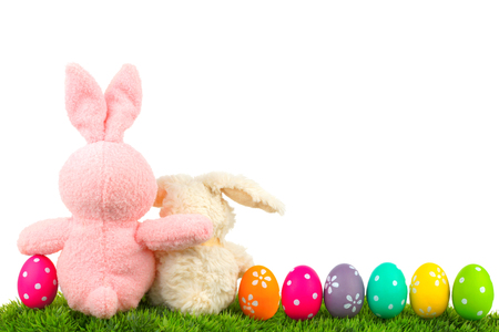 Hugging Easter bunnies on grass with colorful egg border over white behind view Stock Photo
