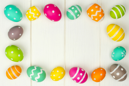 Colorful Easter egg frame against a white wood background photo