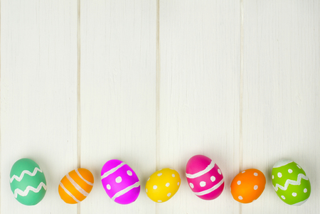 Colorful Easter egg bottom border against a white wood background