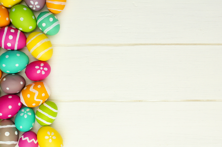Colorful Easter egg side border against a white wood background