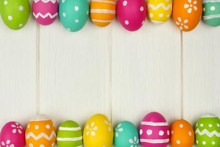 huevo: Marco colorido del huevo de Pascua contra un fondo de madera blanca Foto de archivo