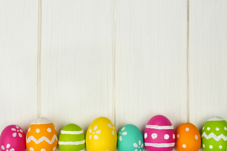 easter and egg: Colorful Easter egg bottom border against a white wood background