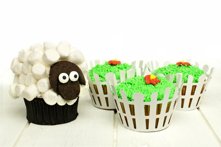 Easter lamb and grass cupcakes on a white wood background photo
