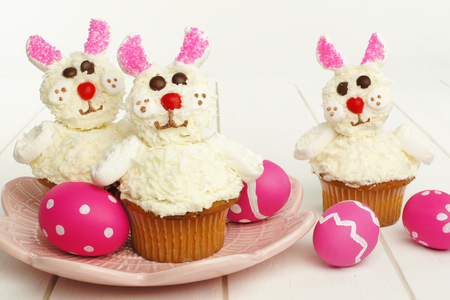 Cute spring bunny cupcakes on pink plate with Easter eggs photo