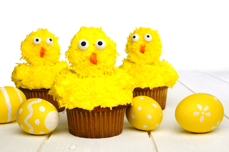 Cute spring chick cupcakes on white wood with Easter eggs photo