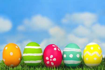Colorful painted Easter eggs on grass with blue sky background