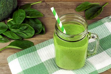 Gezonde groene smoothie met spinazie in een pot mok met geruite doek tegen hout