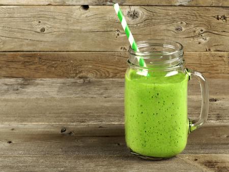 古い木材に石工の瓶マグカップで健康な緑のスムージー