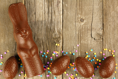 Chocolate Easter eggs and bunny border over a wood background
