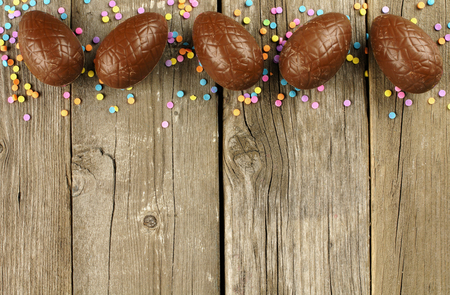 Chocolate Easter egg top border over a wood background