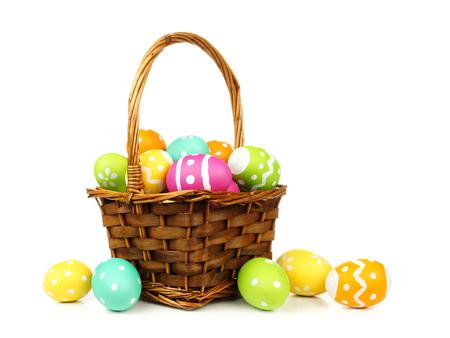 huevo blanco: Canasta de Pascua llena de huevos de colores sobre un fondo blanco Foto de archivo