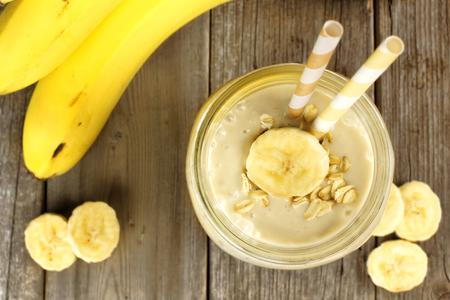 banane: Banana avoine petit smoothie bocal sur la table en bois, vue � la baisse