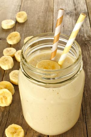 licuado de platano: Plátano avena desayuno smoothie en tarro de albañil en la mesa de madera
