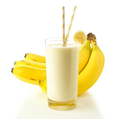 licuado de platano: Batido de plátano en un vaso con pajitas sobre plátanos blancas en el fondo