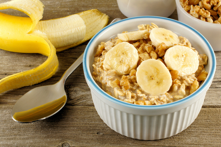 banana: Banana walnut overnight oatmeal in a bowl on wood table Stock Photo
