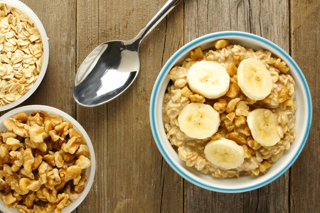 overnight: Banana walnut overnight oatmeal in a bowl on wood table overhead view