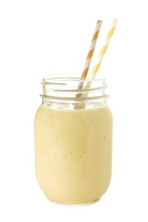 licuado de platano: Batido de plátano en un frasco de vidrio con pajitas sobre blanco Foto de archivo