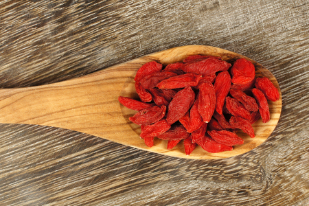 goji berry: Spoon full of dried goji berries over a vintage wood background Stock Photo