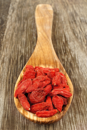 Wooden spoon full of dried goji berries over a vintage wood background photo