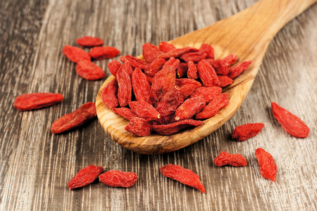 Spoon full of dried goji berries over a vintage wood background photo