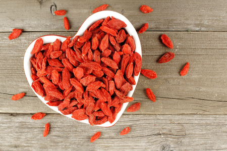 scattered in heart shaped: Heart shaped bowl filled with dried goji berries over a wood background Stock Photo
