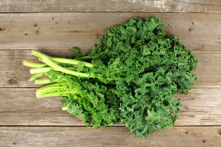 Bunch of fresh kale over a wooden background. Overhead view. Stockfoto