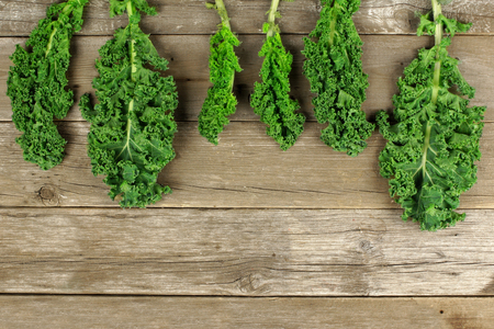 Fresh kale leaves over a wooden background