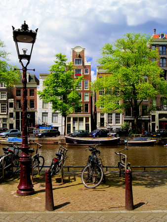 canal street: Amsterdam canal scene with houses, bicycles and street lamp, Netherlands