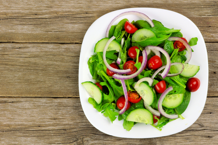 ensalada verde: Ensalada con tomates cherry verdes cebollas rojas y el pepino en un plato blanco con fondo de madera vista a�rea Foto de archivo