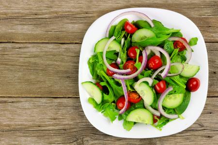 Salat mit Gemüse Tomaten roten Zwiebeln und Gurke auf weißen Platte mit Holz Hintergrund Draufsicht