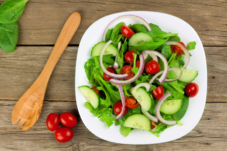 cucumber: Salad with greens cherry tomatoes red onions and cucumber on white plate with wood background overhead view with fork Stock Photo