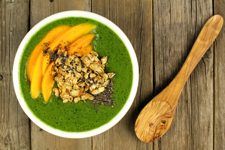 chia: Green smoothie bowl with mangoes granola almonds and chia seeds overhead view on wood with spoon