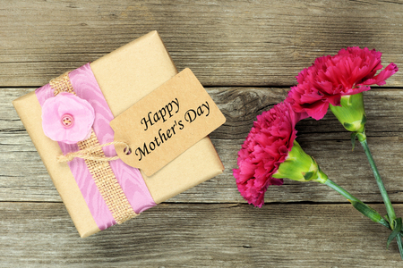 Gift box with Happy Mothers Day tag and carnations against a rustic wood background Zdjęcie Seryjne