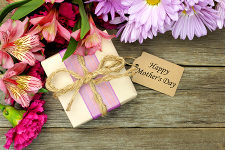 downward: Border of flowers with gift box and Happy Mothers Day tag against a rustic wood background Stock Photo